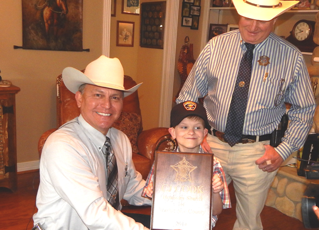 Washington County Sheriff Otto Hanak and Grimes County Sheriff Don Sowell make C.J. Herron the honorary sheriff for both counties
