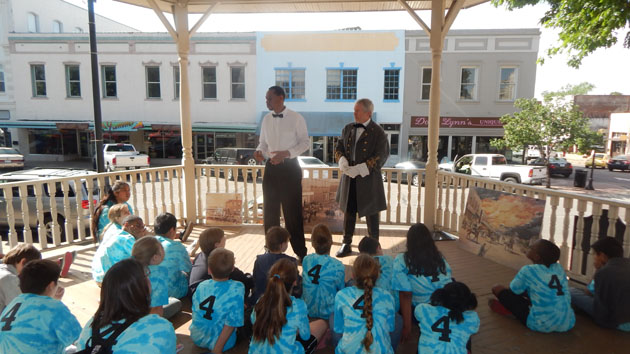 Darron Smith, protraying Brenham educator Henry Foster, and Rich Perkins protraying Banner Press publsher Daniel McGarrity, give fourth graders an insight into the history of Brenham, including the Great Brenham Fire.
